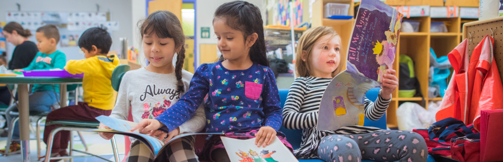 three girls looking at story books in classroom